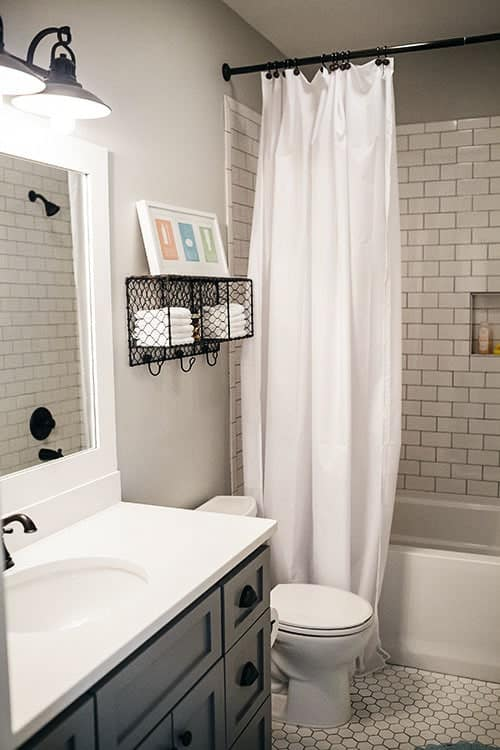 The bathroom is equipped with a bathtub, a toilet under the perforated shelf, and a sink vanity with a large mirror.
