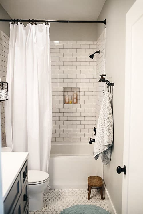 The bathtub has a shower combo that showcases an inset shelf and wrought iron fixtures against the white subway tile walls.