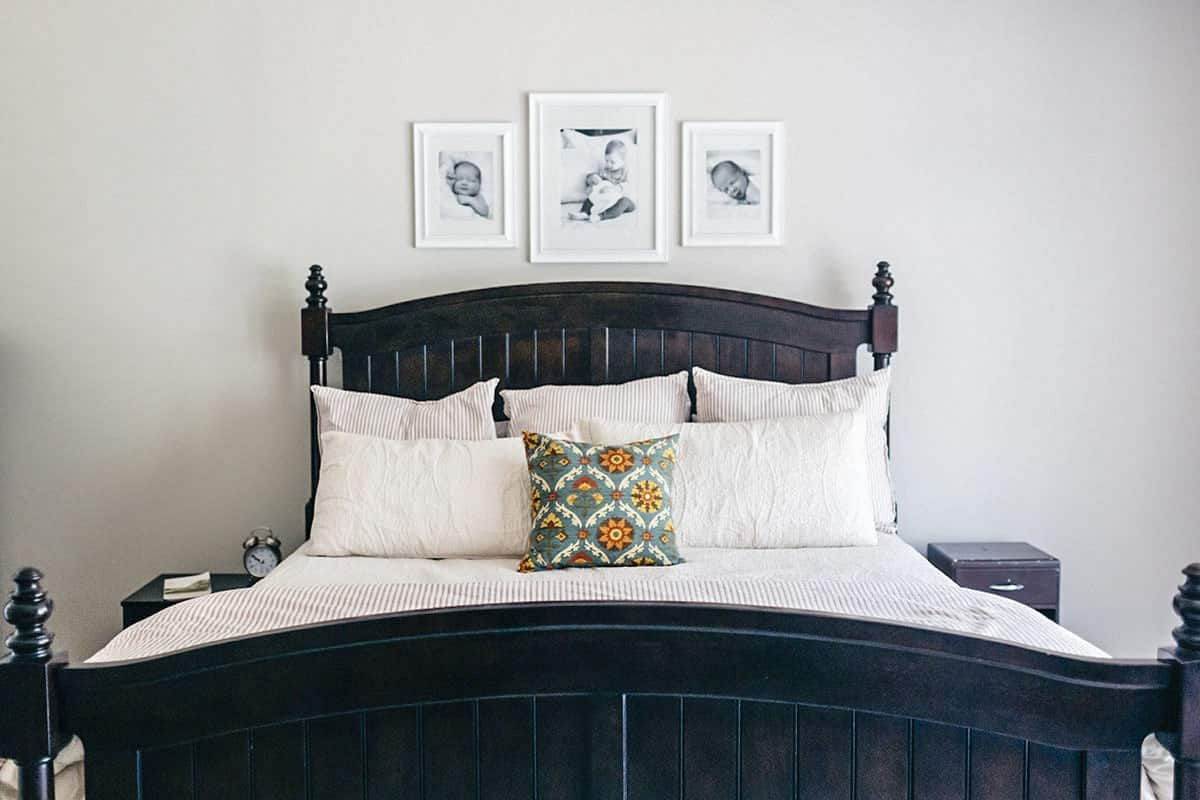 Primary bedroom with dark wood nightstands and a comfy bed under the lovely baby photos.
