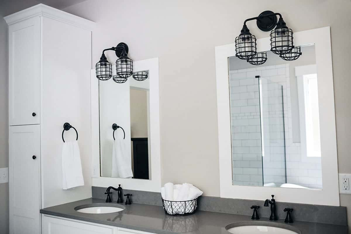 The primary bathroom also offers a tall cabinet and dual sink vanity illuminated by industrial sconces.