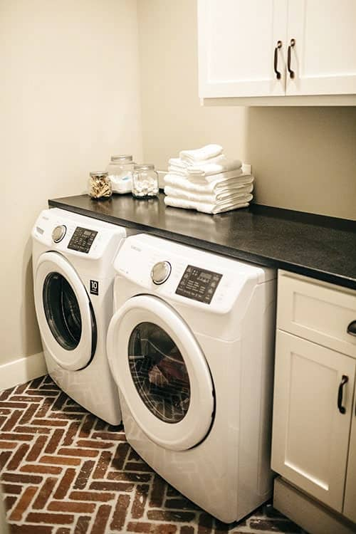 Laundry room with a black granite countertop, washing machine, and dryer over herringbone flooring.