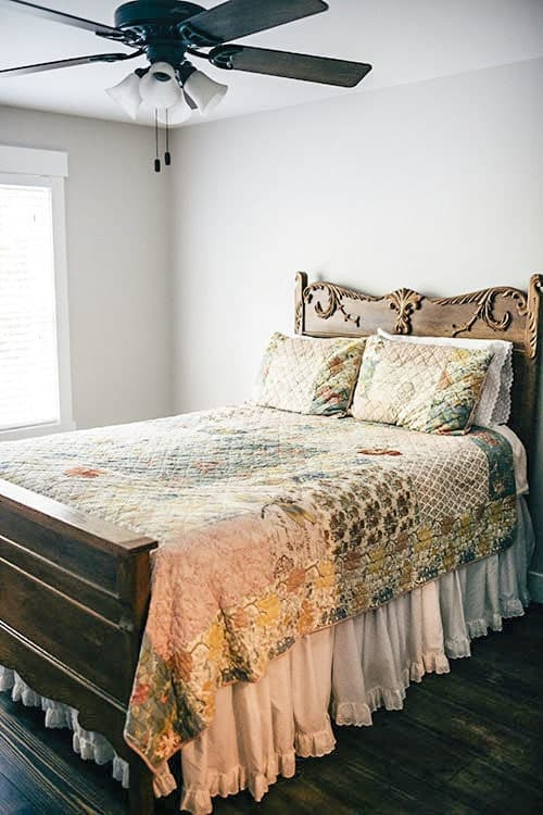 Another bedroom with a ceiling fan and carved wood bed dressed in pattern textured bedding.