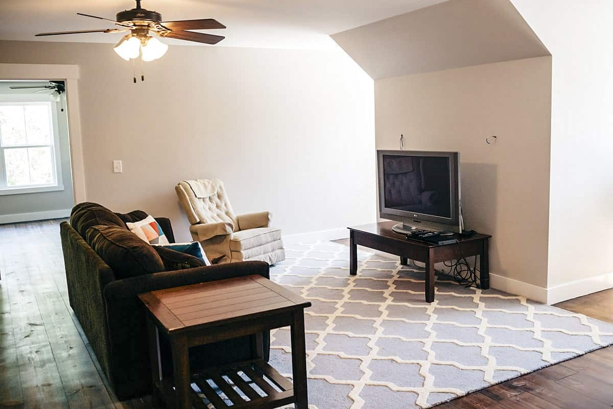 Media room showcases cozy seats, a TV, and wooden tables over a blue patterned rug.