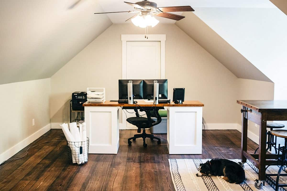 The home office has natural hardwood flooring and a vaulted ceiling mounted with a traditional fan.