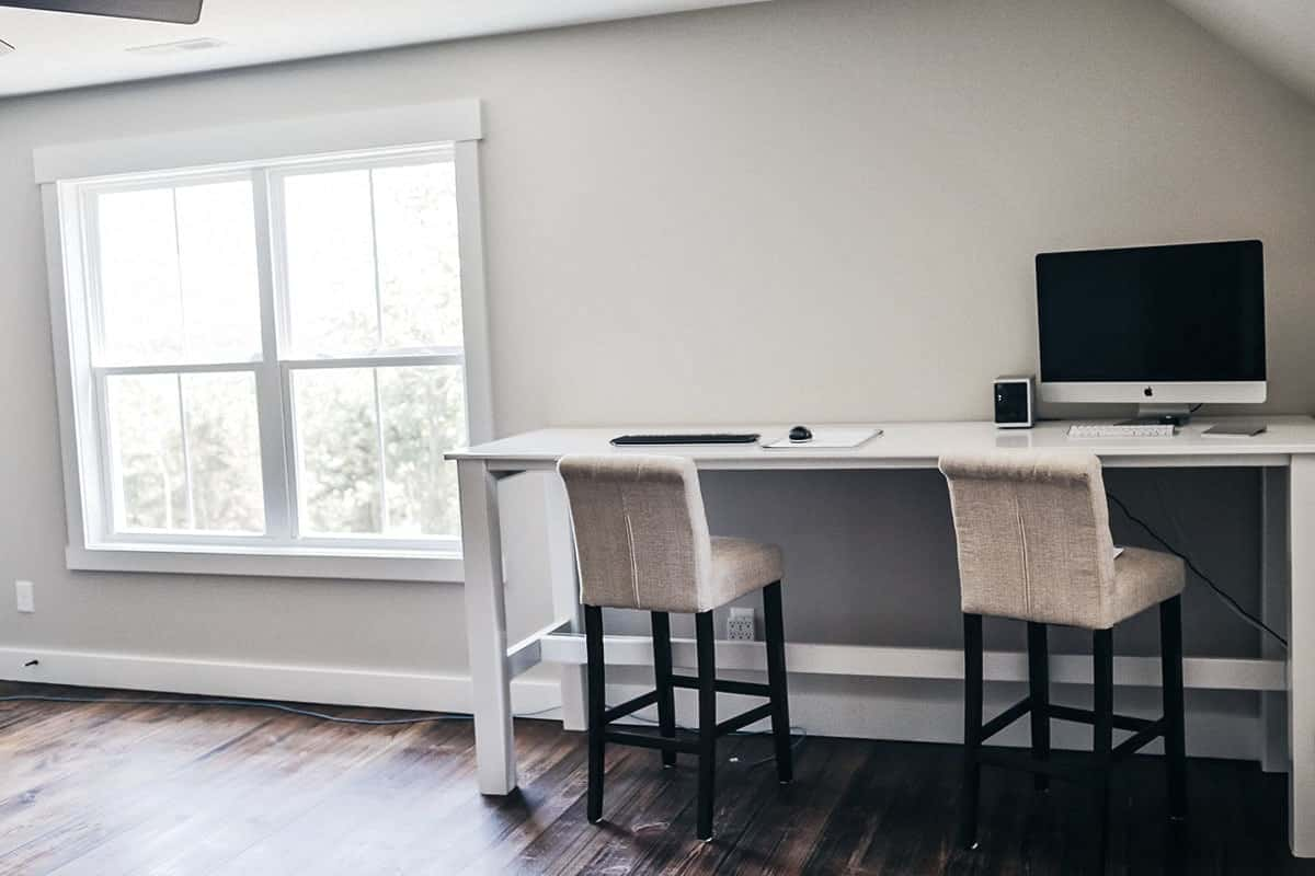 Another home office offering a lengthy white desk and a pair of cushioned chairs matching with the gray walls.