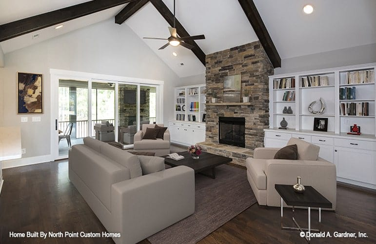 The great room has natural hardwood flooring, stone fireplace and a cathedral ceiling lined with dark wood beams.
