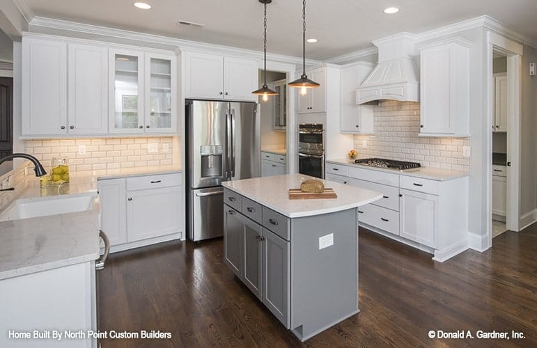 Kitchen with a gray center island, cutting-edge appliances, and white cabinetry matching with the subway tile backsplash.