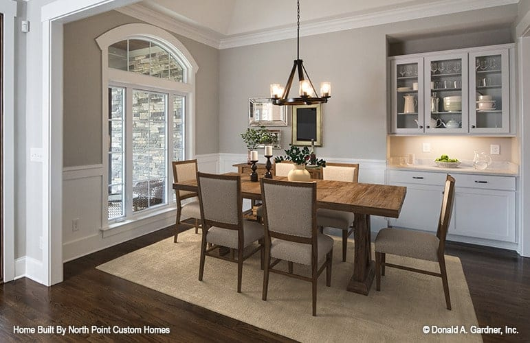The formal dining room offers a buffet cabinet and wooden dining set illuminated by a round chandelier.