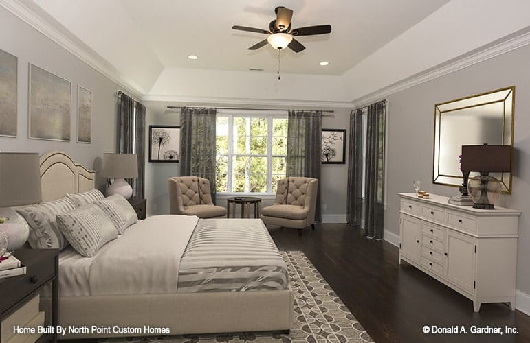The primary bedroom has dark hardwood flooring, a tray ceiling and a sitting area by the white-framed windows.