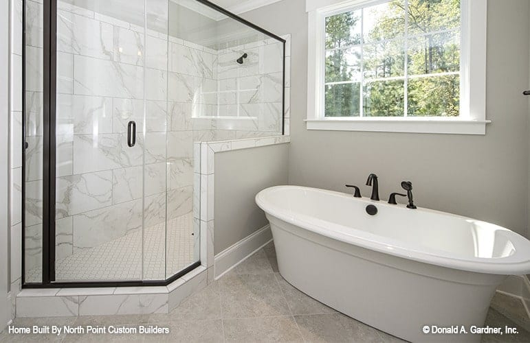 The primary bathroom features a spacious corner shower and a freestanding tub fitted with wrought iron fixtures.