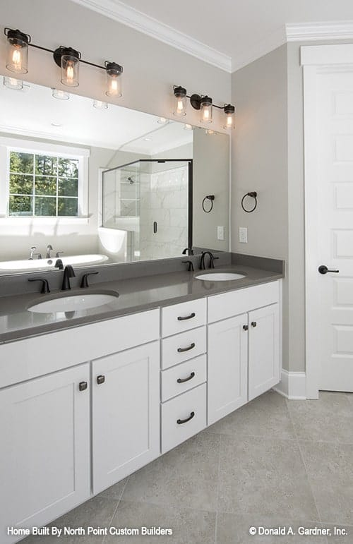 Opposite the tub and shower is the dual sink vanity with gray granite countertop lit by warm glass sconces.