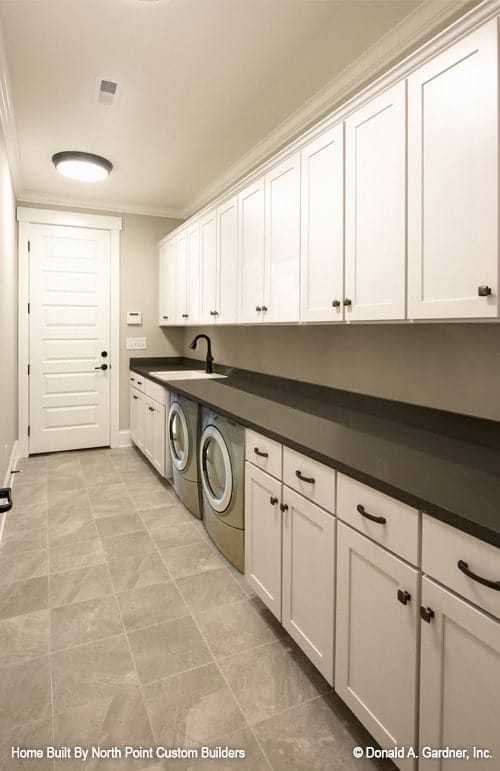 The utility room is equipped with a porcelain sink, front load machines, and white cabinets that run the length of the room.