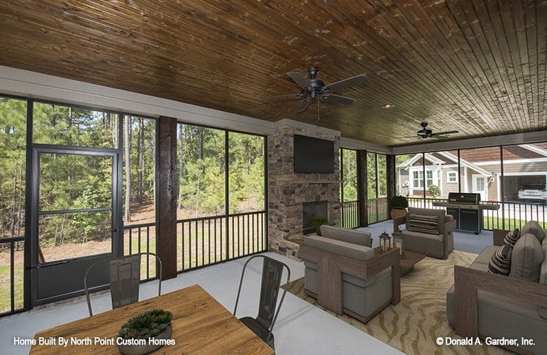 Screened porch with a stone fireplace, multiple seats, an outdoor grill, and wood-paneled ceiling mounted with fans.