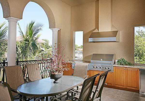 Covered lanai with an outdoor kitchen and an oval dining table surrounded by metal chairs.