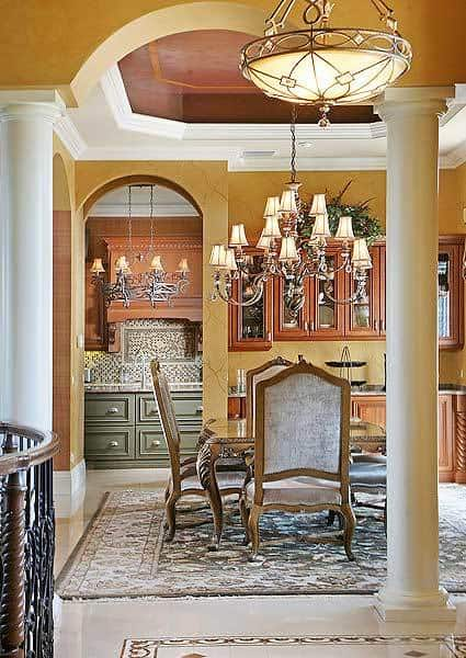 This dining room is defined by a marble column and a beautiful tray ceiling. The archway on the side leads to the kitchen.