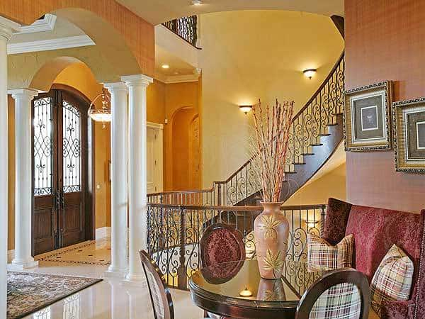 The foyer has a wooden french door and decorative columns supporting the archways leading to the living room.