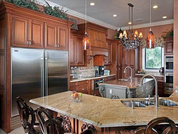 Kitchen with wooden cabinetry, a central island bar, and a curved peninsula lit by warm pendant lights.