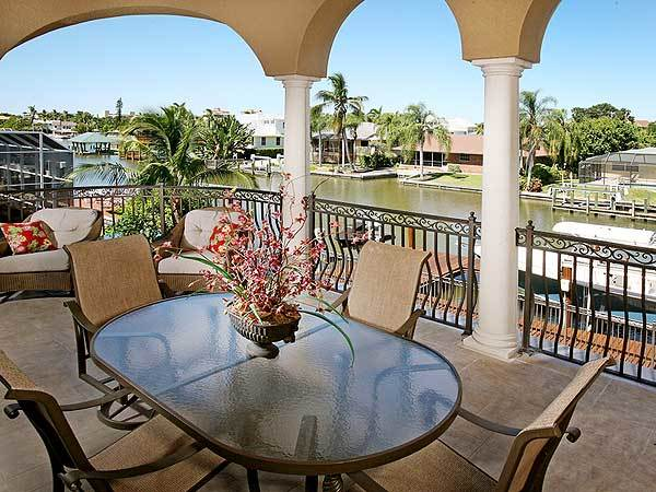 Covered balcony filled with an oval dining set and wicker cushioned chairs that are accented with red floral pillows.