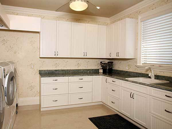 The laundry room is equipped with a washing machine, dryer, white cabinets, and a porcelain sink fitted on the granite countertop.