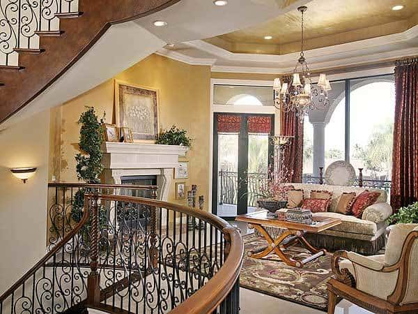 Living room with cozy seats, a warm fireplace, and a gorgeous tray ceiling mounted with recessed lights and a classic chandelier.