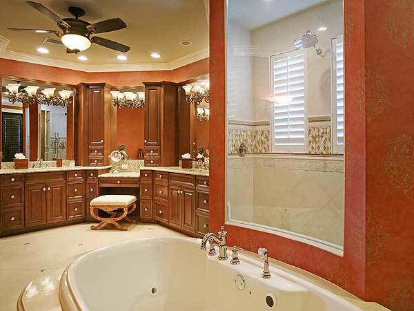 The primary bathroom features a massive dual sink vanity and a deep soaking tub fixed in front of the shower area.