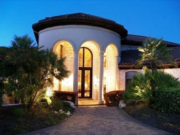 Home's entry with a circular portico and a tall french front door framed with decorative arches.