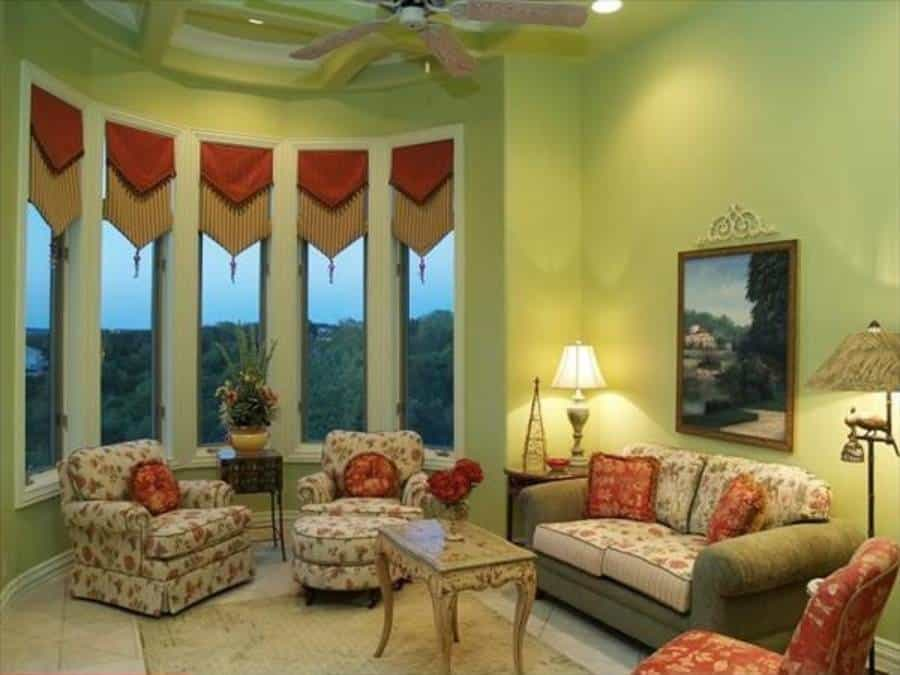 Living room with charming seats, coffered ceiling, and glass-paneled windows dressed in striped valances.