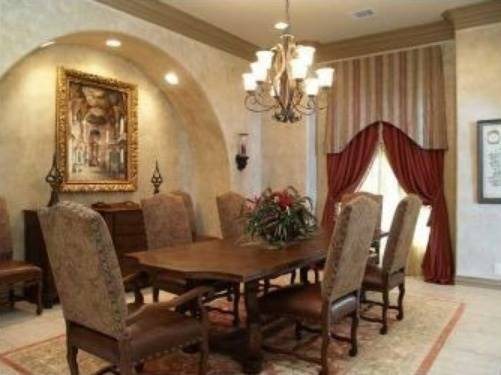 Formal dining room with a wooden dining set and an arched inset niche filled with a buffet table and leather cushioned chairs.