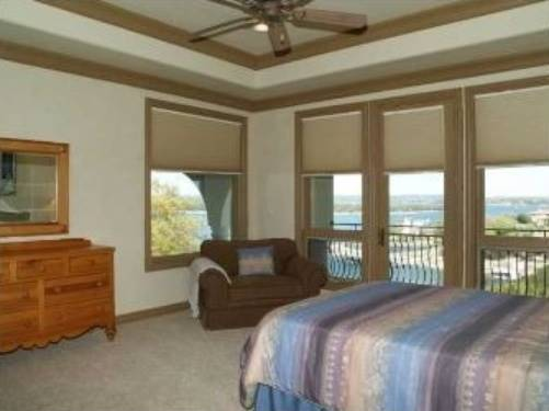 Bedroom with a tray ceiling and wooden framed windows overlooking the balcony with a breathtaking view.
