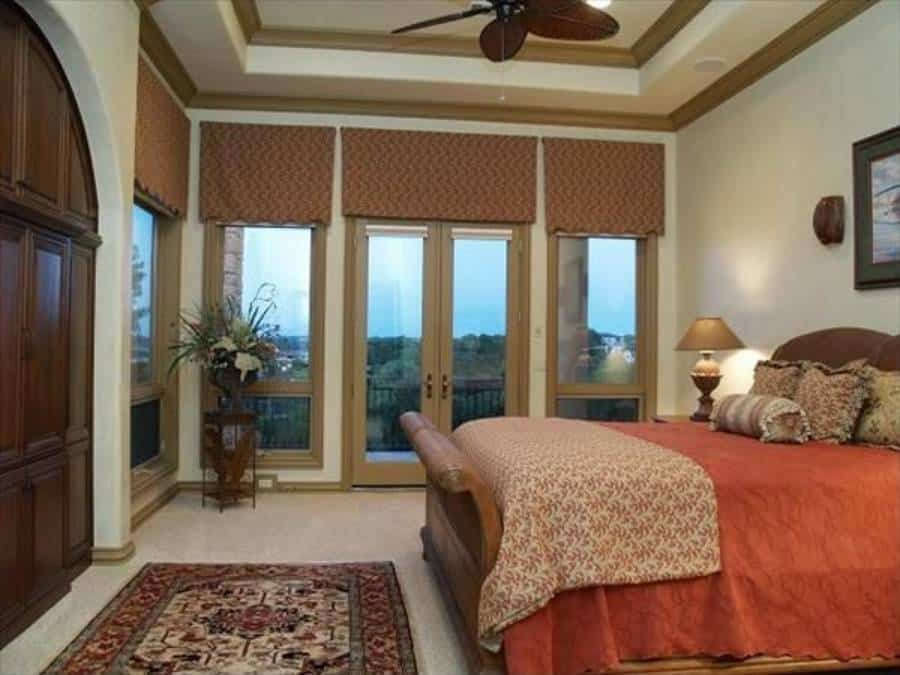 The primary bedroom has the same tray ceiling and a french door that opens out to the balcony.