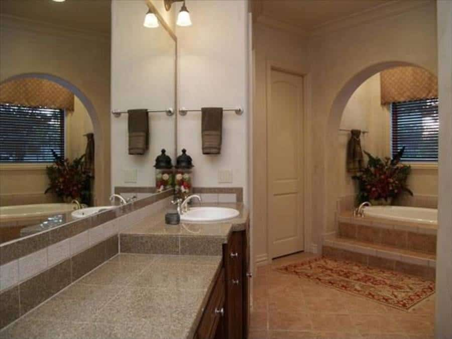 The primary bathroom is equipped with large sink vanity and an alcove bathtub complemented with a red patterned rug.
