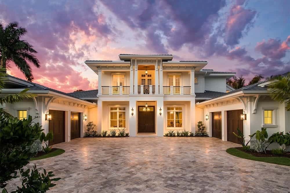 This charming two-story Tropical-style home has a pair of large garages flanking the large courtyard in front of the main entry.