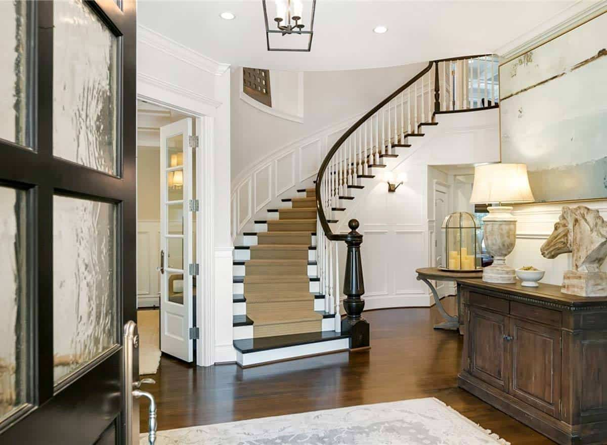 Foyer with a winding staircase and a rustic console table topped with a table lamp and a horse head sculpture.