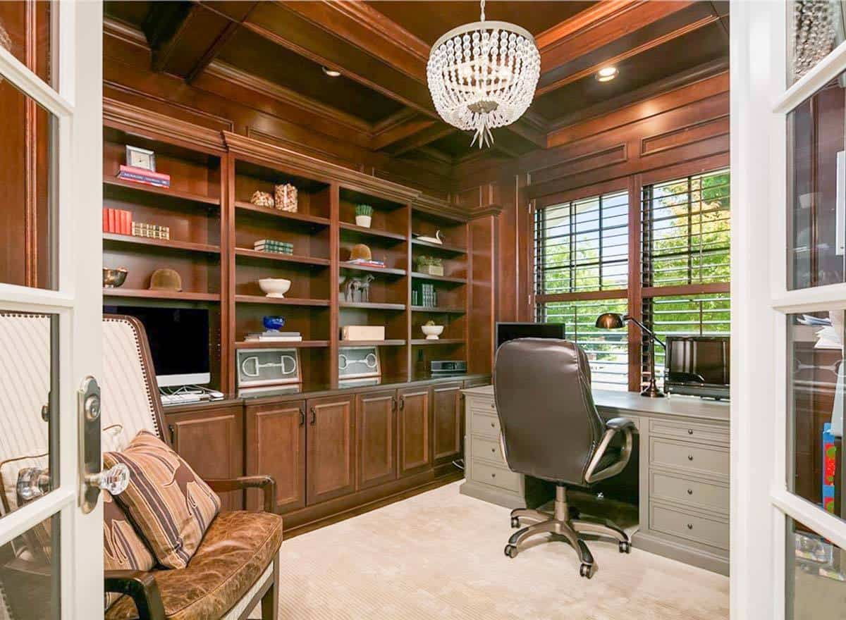 The home office is filled with a gray desk, leather swivel chair, cozy high back seat and built-in shelving matching the wooden coffered ceiling.