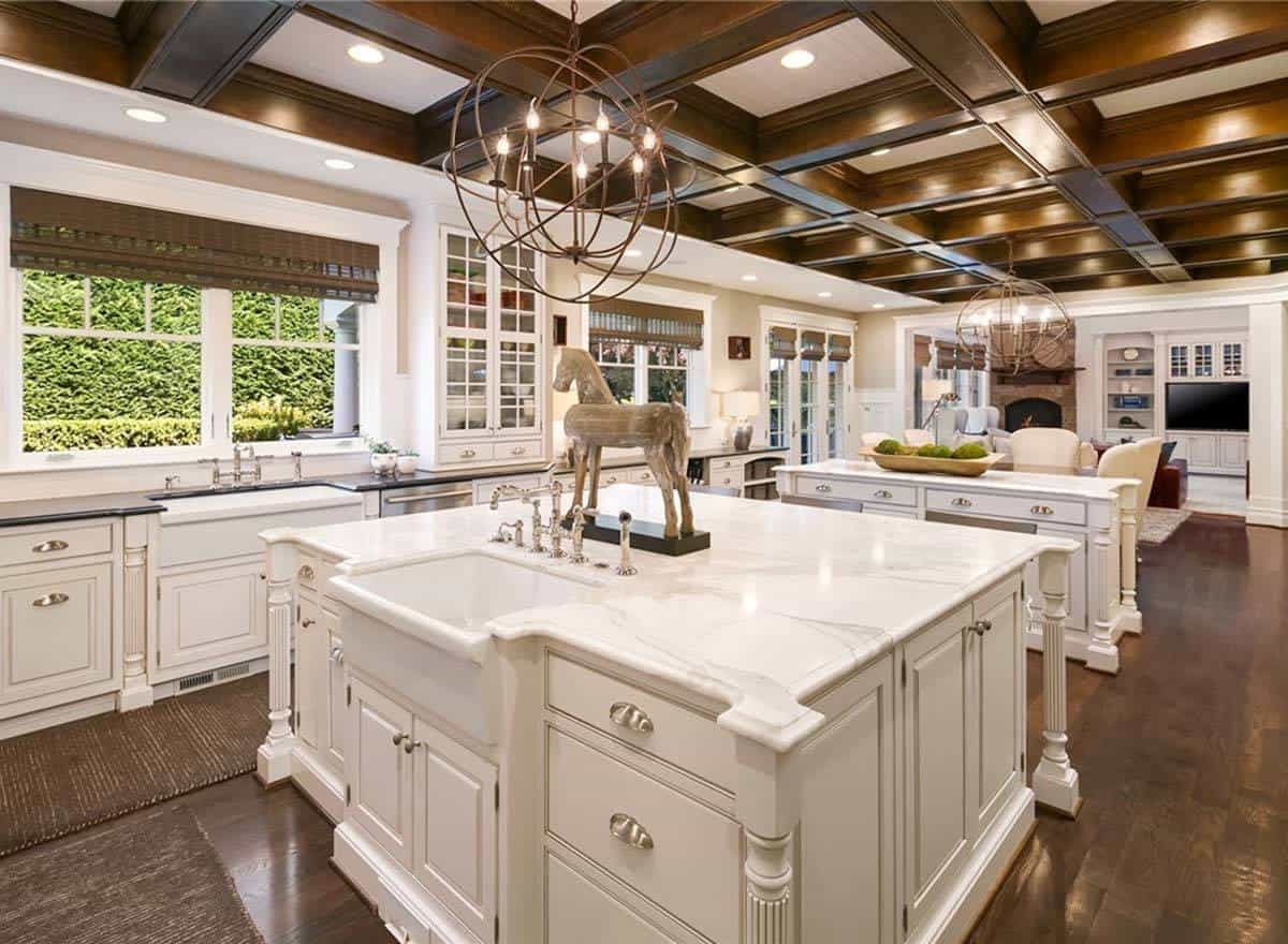 The kitchen features two massive islands that are illuminated with spherical chandeliers hanging from the wooden coffered ceiling.