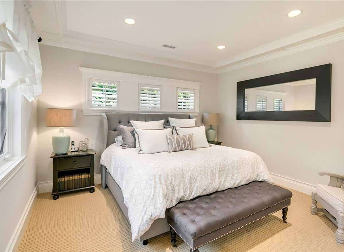 The other bedroom with a rectangular mirror and a wingback bed complemented with a tufted bench.