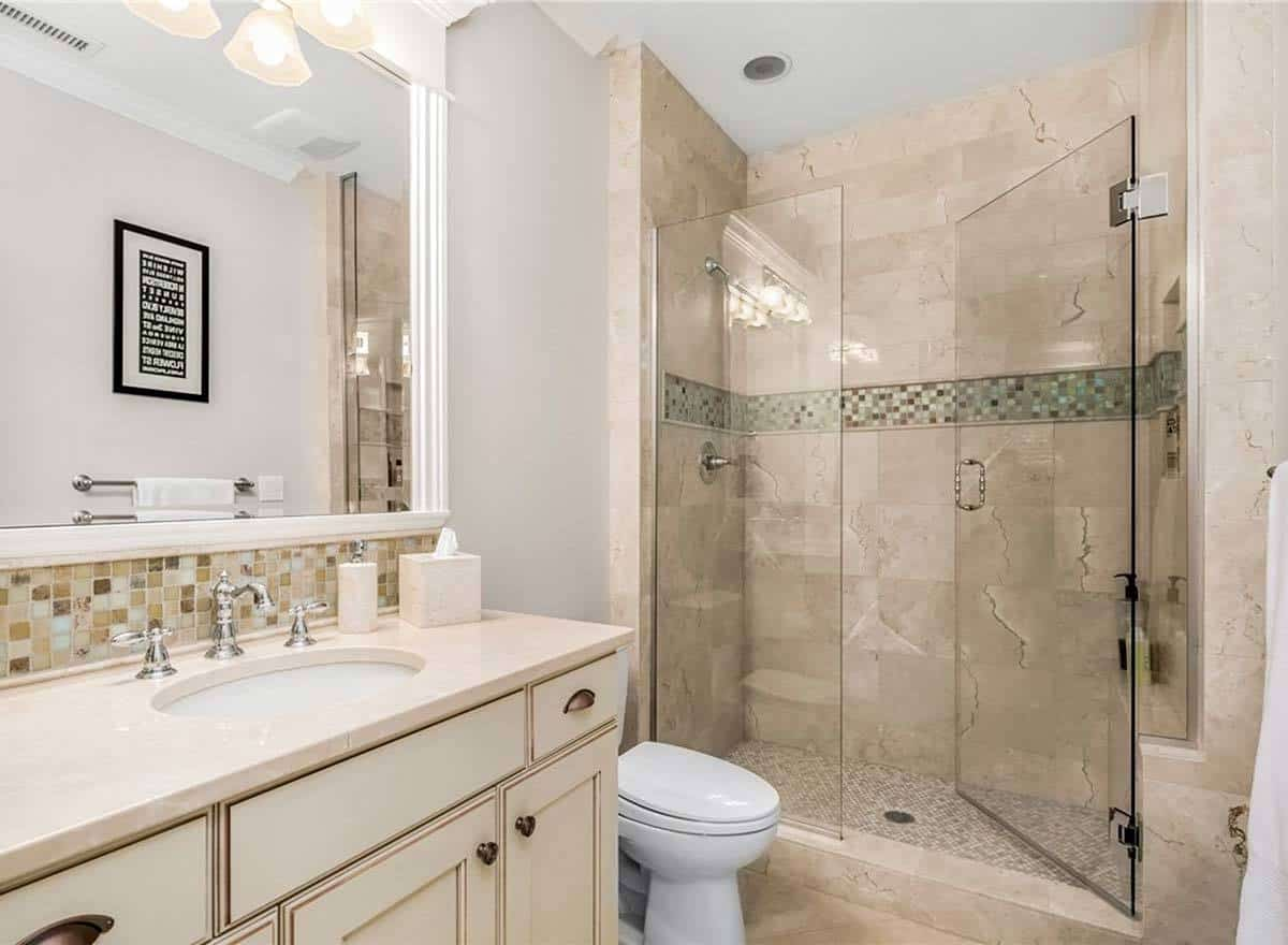 This bathroom showcases a marble top vanity, a toilet, and a walk-in shower enclosed in frameless glass.