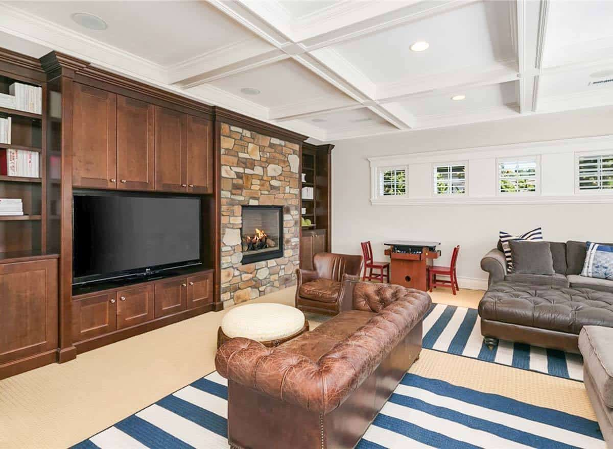 Media room with cozy leather seats and a stone fireplace situated next to the TV.