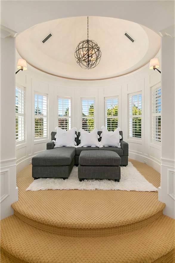 A turreted sitting room with gray sofa and matching ottoman surrounded by the louvered windows.