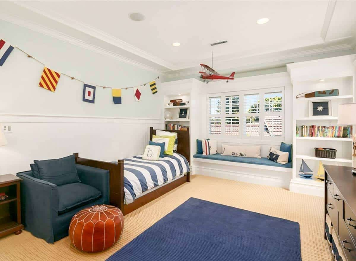 Kid's bedroom with a gray armchair, single bed and a window seat flanked by built-in shelvings.