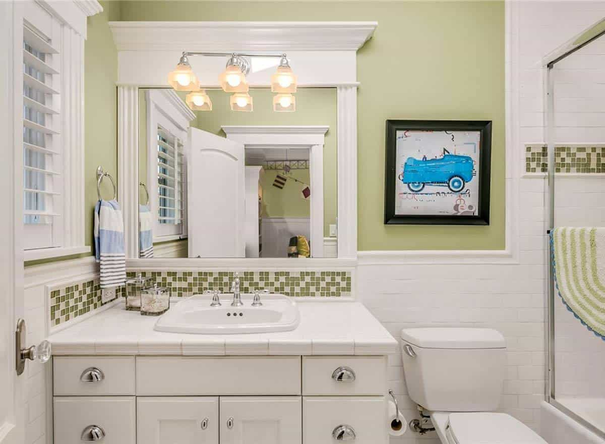 Kid's bathroom with a walk-in shower, a toilet under the car artwork, and a white vanity lit by warm sconces.