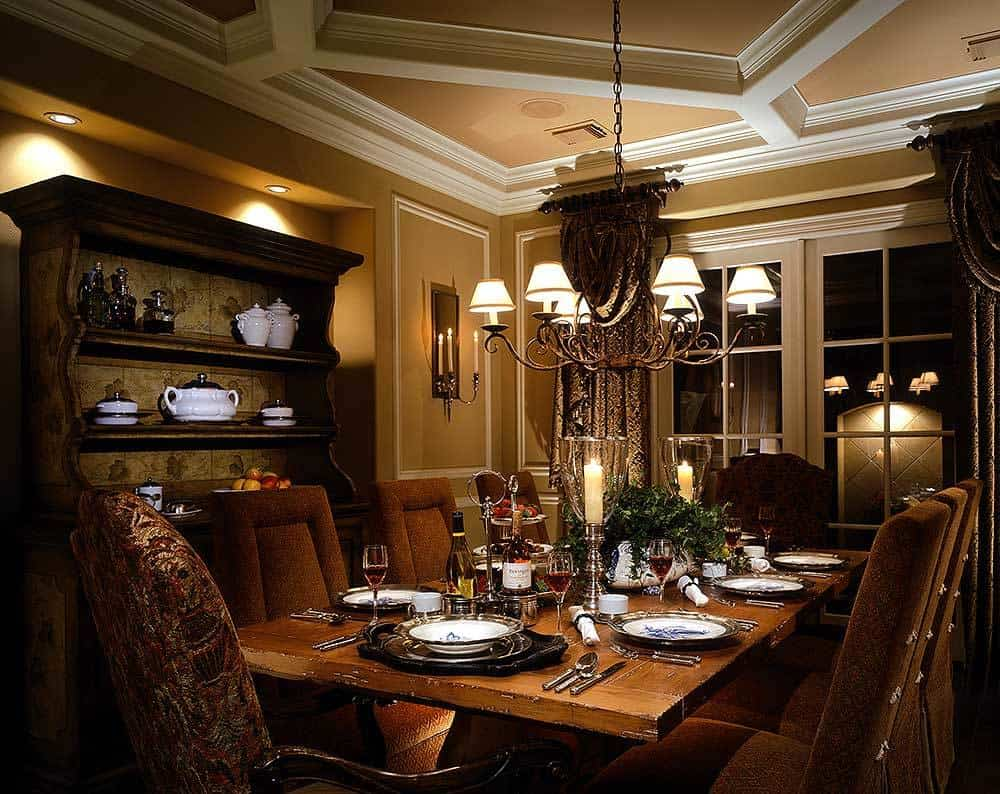 The formal dining room offers an antique cabinet, an ornate chandelier, and a wooden dining table surrounded with elegant upholstered chairs.