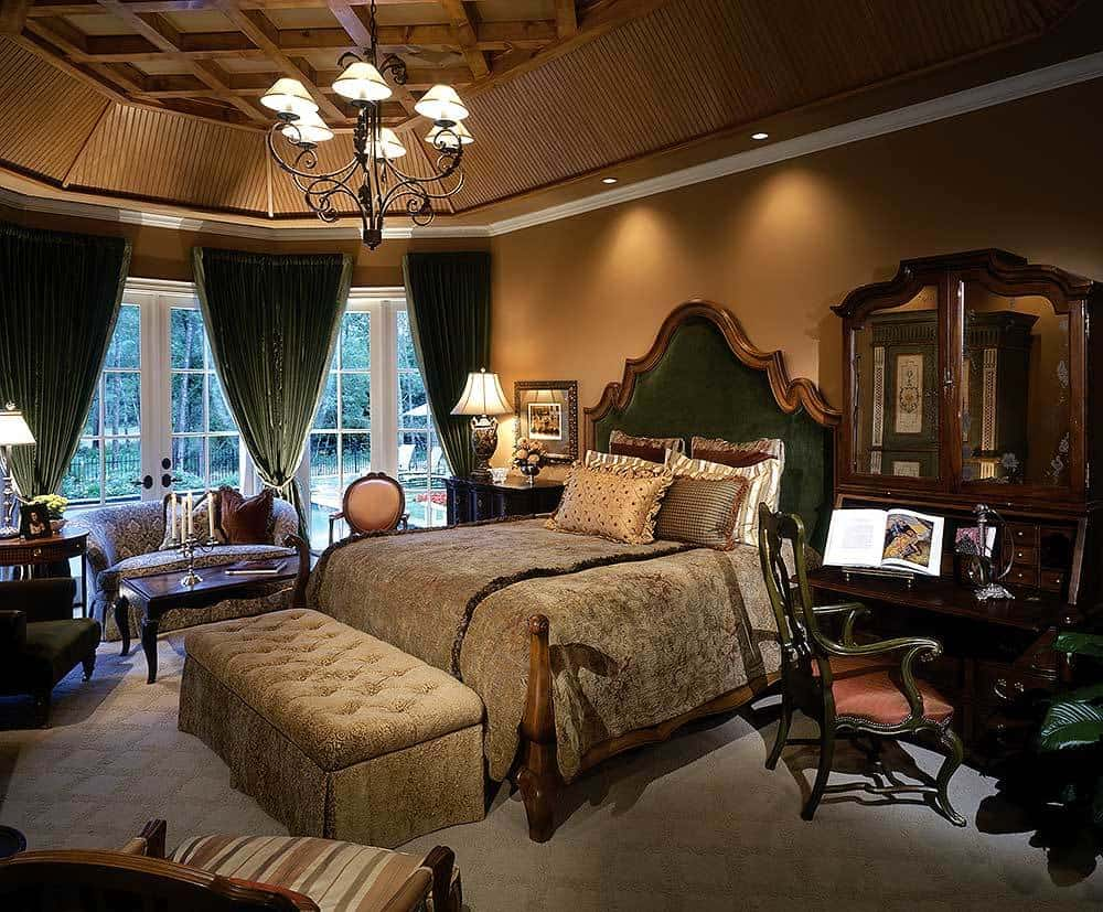 The primary bedroom boasts a magnificent tray ceiling, dark wood furnishings, and a sitting area by the bay window dressed in green draperies.