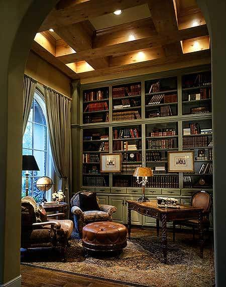 Home office with wooden coffered ceiling, a massive arched window, and a built-in bookcase that runs the length of the room.