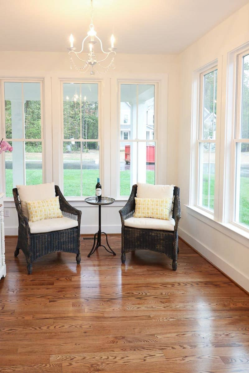 Sitting area by the white-framed windows filled with a pair of wicker chairs and a small round side table.