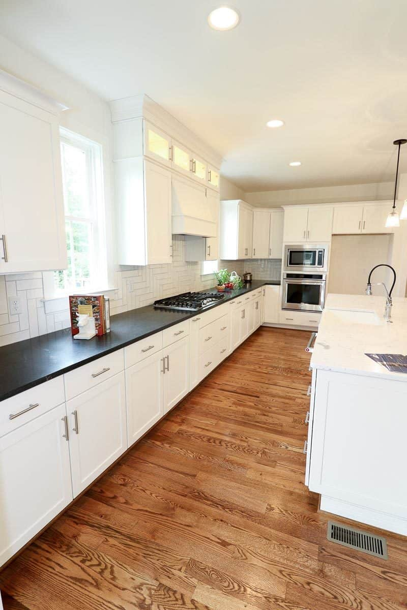 The kitchen includes white cabinetry and tiled backsplash beautifully contrasted with absolute black granite countertop.