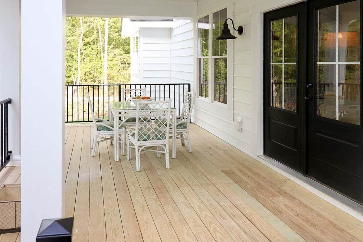 The dark wood french door leads out to the covered patio with white cushioned chairs and a glass top table.