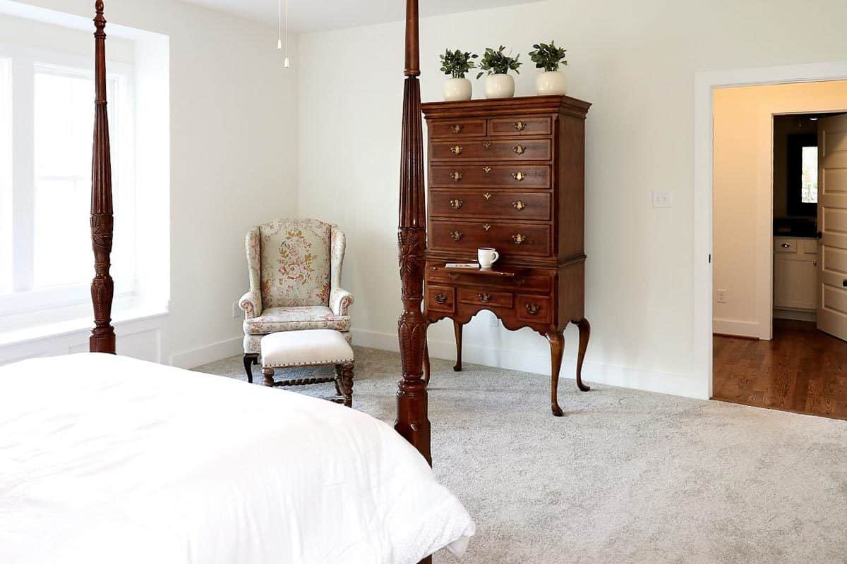 A clawfoot dresser and floral wingback chair complement the four-poster bed.