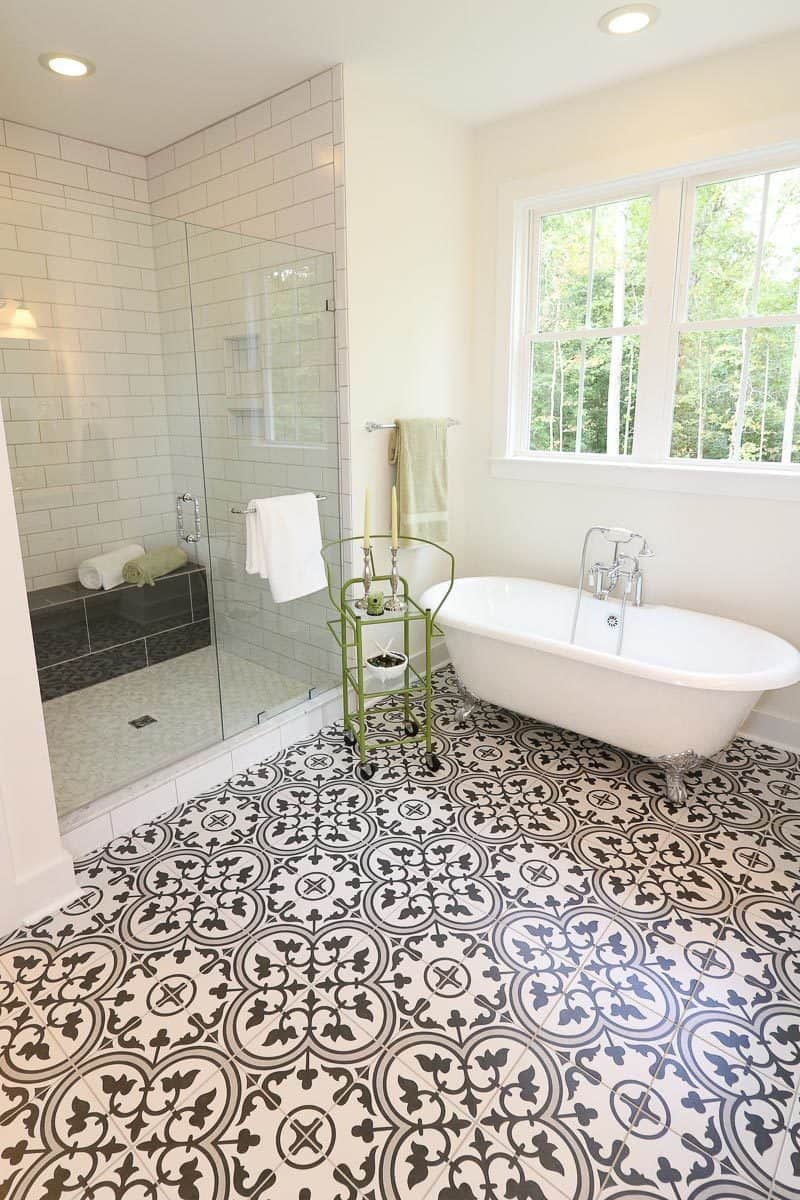 Next to the tub is the walk-in shower with a glass door and a tiled bench.