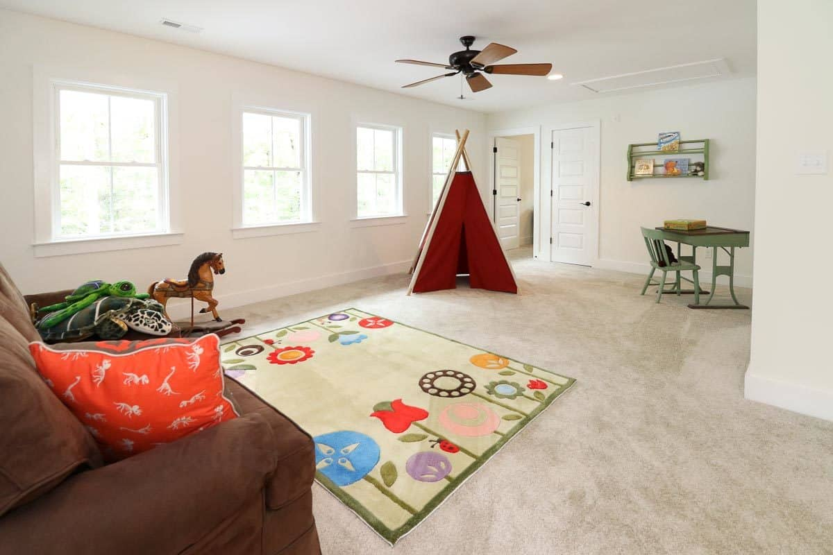 Kid's playroom with brown seat, red tent and a green desk matching with the cute rug.